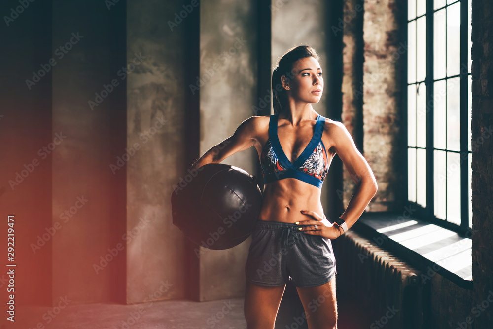 Fototapeta Strong girl holding med ball and looking to the camera. Girl in a gym trains with the ball. Health, sport concept.