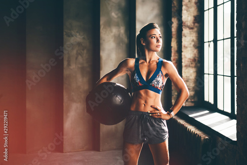 Strong girl holding med ball and looking to the camera. Girl in a gym trains with the ball. Health, sport concept. - 292219471