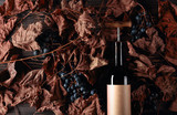 Bottle of red wine with corkscrew. On a table dried vine leaves and blue grapes. - 292223643