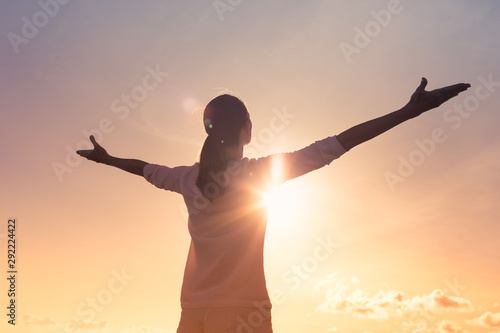 Fototapeta It's a new day concept. Happy woman in the sunshine lifting arms up to the sky.  obraz