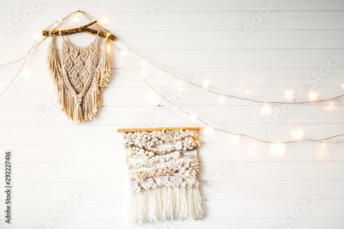 фотография Macrame hanging on white wooden wall with lights