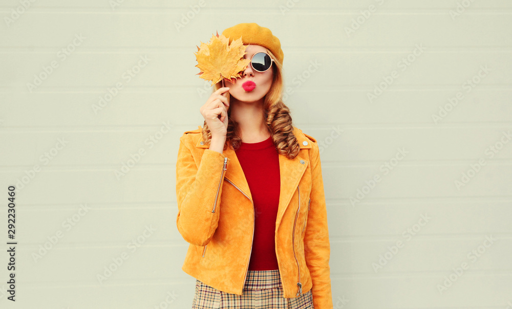 Fototapeta Autumn portrait woman holding in her hands yellow maple leaves hiding her eye, girl blowing red lips sending sweet air kiss over gray wall background