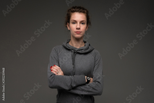 Portrait of young woman in grey hoodie against gloomy background isolated Wallpaper Mural