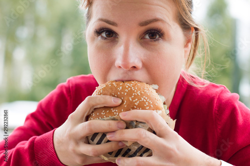 Cuadros en Lienzo Close up portrait of hungry girl is eating fast street junk food