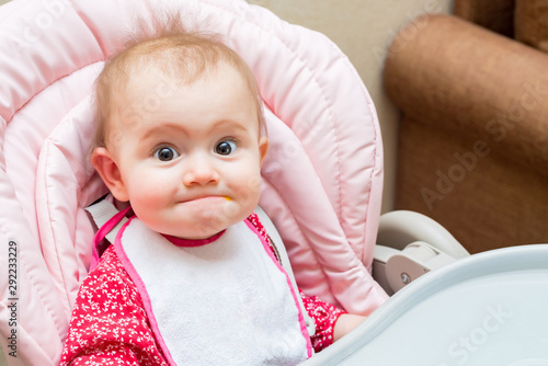 Obraz Funny baby girl while being fed in her pram - fototapety do salonu