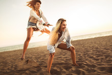 Happy Women On The Beach Playing Leap Frog, Having Fun, Selective Focus.