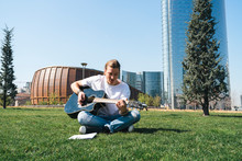 Man Composing Music In Urban Garden Playing Guitar And Reading Script