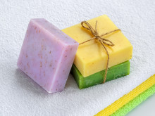 Yellow, Green And Purple Handmade Herbal Soap Bars On A Terry Cotton Towel. Natural Toiletries And Hygiene Products With Herbs And Essential Oils.
