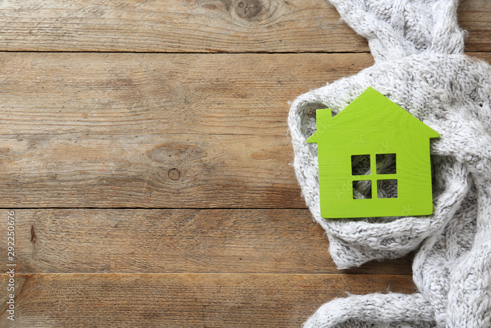 Fototapeta House model and scarf on wooden background, top view with space for text. Heating efficiency