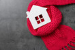 canvas print picture - Wooden house model and red scarf on grey stone background, top view. Heating efficiency