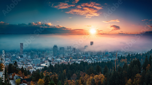 Portland downtown with rolling fog and autumn foliage in shining sunrise and colorful clouds - 292256269