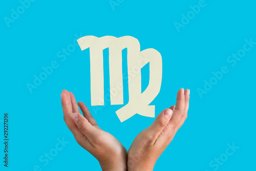 Virgo astrological sign hanging over female hands on blue background, horoscope Canvas Print