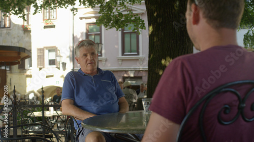 CLOSE UP: Father and son talking while sitting in a cafe on a sunny summer day Canvas Print