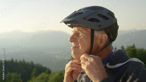 Fototapeta  CLOSE UP: Focused senior man straps up his helmet before an evening bicycle ride