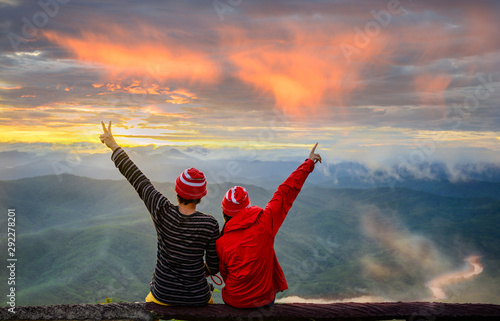 couple lover enjoy the morning sunrise nature on the peak top of rainforest moun Wallpaper Mural