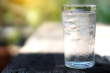 A Glass Of Water With Ice On Nature Background