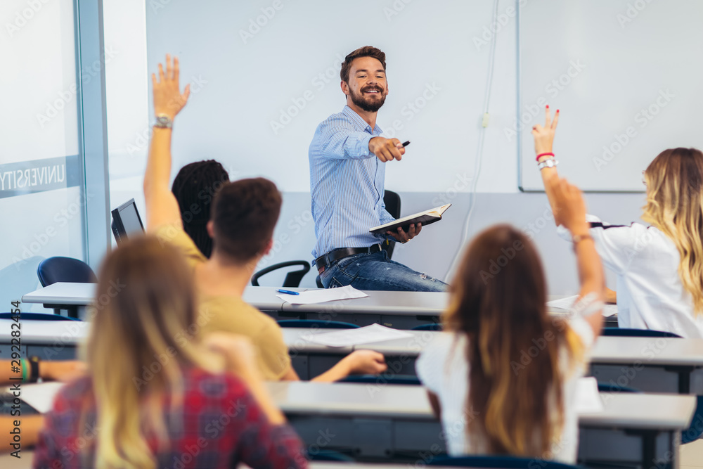 Fototapety, obrazy: Group of students raising hands in class on lecture