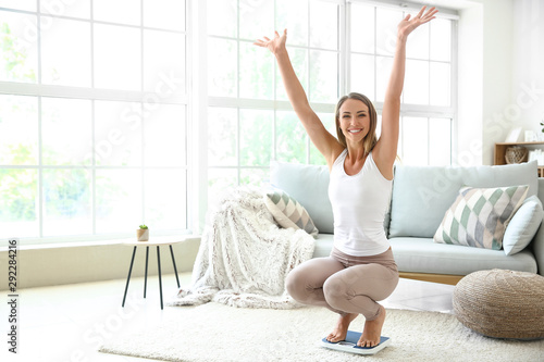 Cuadros en Lienzo Happy young woman on scales at home. Weight loss concept