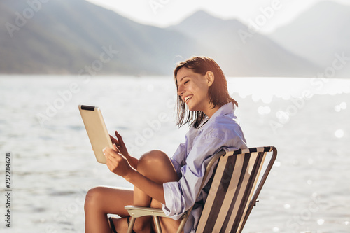 Smiling woman sitting on deck chair by the sea using tablet on a sunny day Fototapet