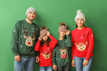 Happy Family In Christmas Sweaters On Color Background