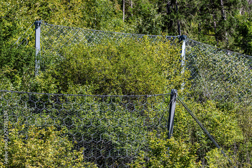Fotografie, Obraz Close-up of a rockfall (brake for rocks fall) barrier with wire mesh in mountain