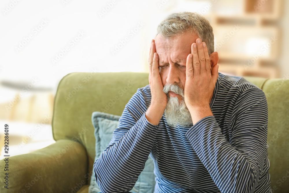 Fototapeta Senior man suffering from headache at home