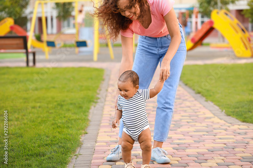 Fototapeta  African-American mother teaching her little baby to walk outdoors