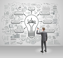 Businessman Drawing Business Idea Light Bulb On Wall. Graphic Doodles Vector Illustration Style.