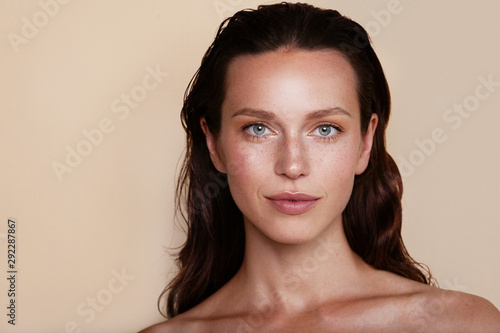 Beauty woman portrait. Beautiful spa model girl with perfect fresh clean skin. Youth and skin care concept. Beige background. Nude makeup