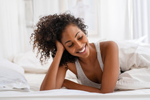 Smiling Young Woman Lying On Bed