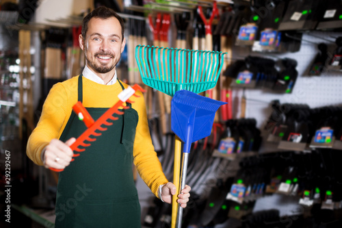 Seller displaying various items in garden equipment shop Canvas Print