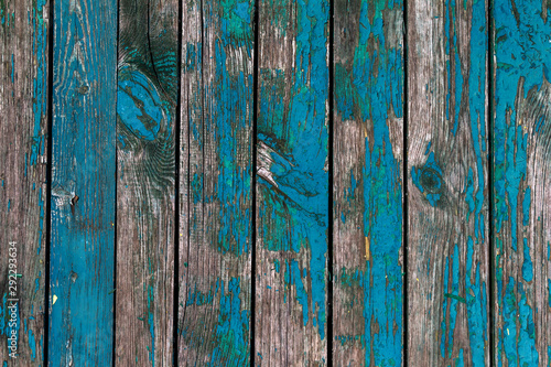 Old shabby wooden boards with cracked paint, background. Background old wood with large cracks and traces of the remains of old paint