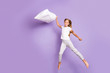 Leinwanddruck Bild - Full size photo of cheerful funny funky model preteen girl hold pillow jump have fight sleep-over party with friends enjoy weekend barefoot wear white t-shirt pants isolated violet color background