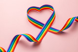 Fototapeta Tęcza - LGBT rainbow ribbon in the shape of heart. Pride tape symbol. Pink background