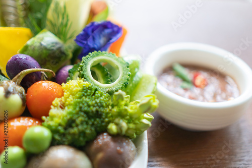 фотография  Beautiful fresh vegetable decoration on white plate with spicy shrimp paste dip thai food style