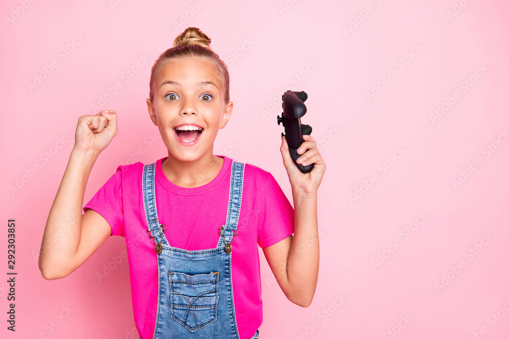Fototapety, obrazy: Photo of excited cute nice blonde preteen girl having won contests at video games celebrating victory wearing fuchsia t-shirt jeans denim isolated over pink pastel color background