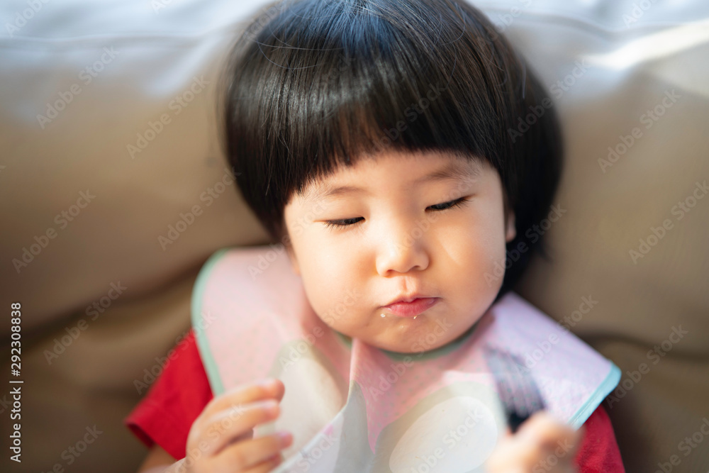 Fototapety, obrazy: Adorable healthy 2 years old Asian toddler enjoys her snack, eating by herself using a hand and fork while looking happy in the living room, selective focus in concept toddler learning to eat food.