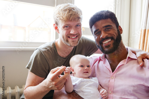 Photo  Portrait Of Loving Male Same Sex Couple Cuddling Baby Daughter On Sofa At Home T