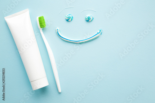 Fotografie, Obraz  Toothbrush with green bristles, white tube of toothpaste on pastel blue background