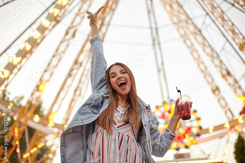 Foto Positive young beautiful brunette woman posing over attractions in amusement par