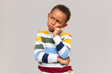 Waist Up Shot Of Moody Grumpy African Schoolboy In Sweater Holding Hand On His Face, Pouting Lips And Frowning, Sulking With His Greedy Friend Who Does Not Want To Share Toys. Complain Or Disagreement