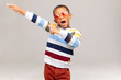 Cheerful emotional Afro American boy of school age having fun, opening mouth widely as if singing and keeping hands, making dance move, posing in studio wearing round pink sunglasses and sweater