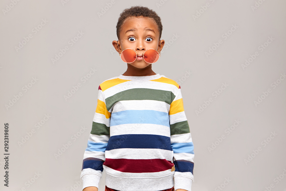 Fototapety, obrazy: Oops. Funny bug eyed dark skinned little boy in stylish multicolored jumper staring at camera in full disbelief, round pink sunglasses slipped off his eyes. Surprise, shock and astonishment