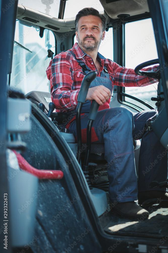 Fototapeta Farmer working on a modern tractor