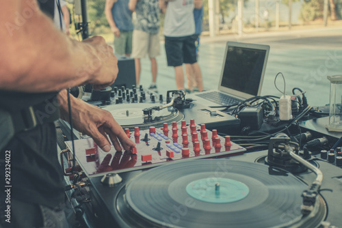 Outdoor music party. Dj playing on vinyl. Dj's hands and turntable close up, blurred people on the background - 292324022