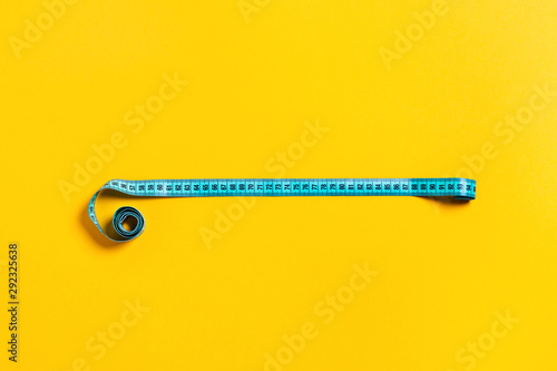 Diet concept, tape measure on yellow background. Wallpaper Mural