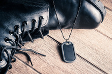 Black Rubber Edge Military Dog Tag With Some Part Of Black Genuine Leather Combat Boots On The Old Wooden Floor