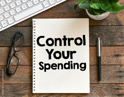 Fotografía  Control your spending text written in a notebook as a concept
