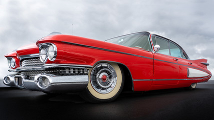 Side view of a classic american car from the fifties. Low angle view showing red paint and chrome fender and grill.