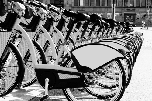 Photo sur Toile Velo Row of bicycles parked. Row of parked colorful bicycles. Rental bicycles. Pattern of vintage bicycles bikes for rent on sidewalk. Close up of wheel. Soft lighting. Black and white